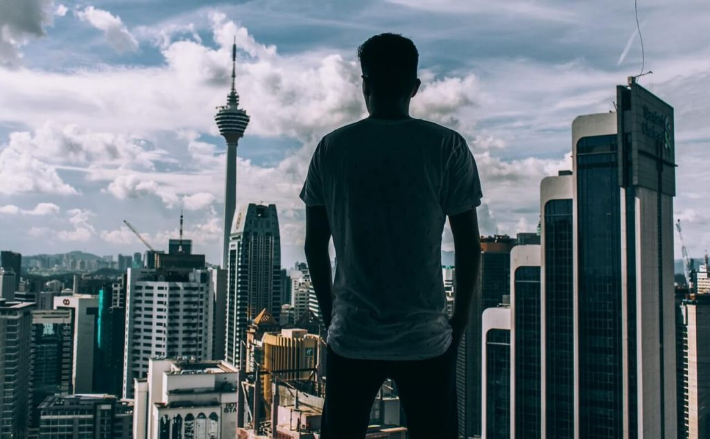 Man standing near window and staring at tall city buildings
